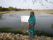 One of the cooperative members in boyershing village with the groups aquaculture pond